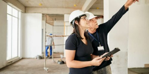 Shot of a chief supervisor pointing at the roof and discussing with a female engineer holding a digital tablet at a construction site